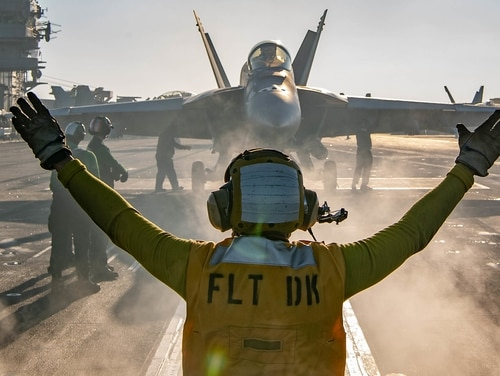 A sailor directs an F/A-18E Super Hornet on the flight deck of the aircraft carrier Nimitz during flight operations on Jan. 17, 2021 in the Arabian Sea. (MC3 Charles DeParlier/U.S. Navy)
