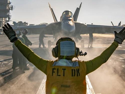 A sailor directs an F/A-18E Super Hornet on the flight deck of the aircraft carrier USS Nimitz (CVN 68) during flight operations on Jan. 17, 2021, in the Arabian Sea. (MC3Charles DeParlier/Navy)