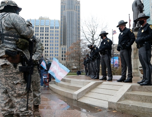 Ohio state troopers provide security at the Ohio Statehouse as armed protestors look on Sunday, Jan. 17, 2021, in Columbus, Ohio. Security was stepped up at statehouses across the U.S. after FBI warnings of potential armed protests at all 50 state capitols and in Washington. (Jay LaPrete/AP)