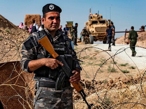 A member of Kurdish security forces stands guard during a demonstration by Syrian Kurds against Turkish threats next to a base for the U.S.-led international coalition on the outskirts of Ras al-Ain town in Syria's Hasakeh province near the Turkish border on Oct. 6, 2019. - (Delil Souleiman/AFP via Getty Images)