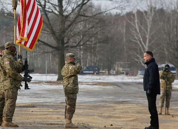 Polish President Andrzej Duda, right, stands in front of a saluting U.S. Army soldier during the opening of joint Polish and U.S. exercise on training fields in Zagan, Poland, Monday, Jan. 30, 2017. (AP Photo/Krzysztof Zatycki)