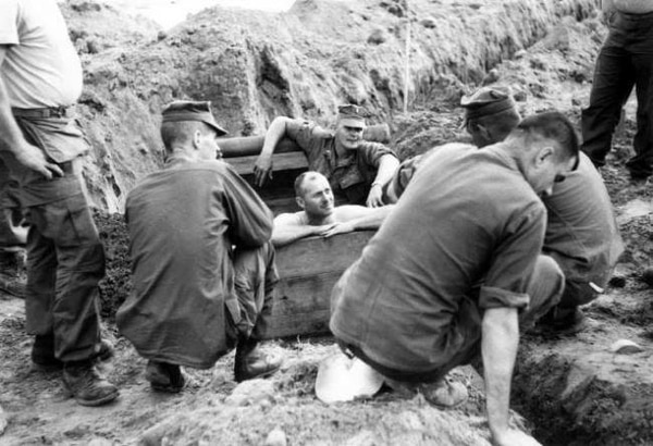 Nearly a decade before he assumed the post of Eighth Sergeant Major of the Marine Corps in 1977, then-1stSgt John R. Massaro (center, shirtless) helped build a septic tank along side the officers and staff noncommissioned officers of Support Company, 3d Engineer Battalion, Third Marine Division.
