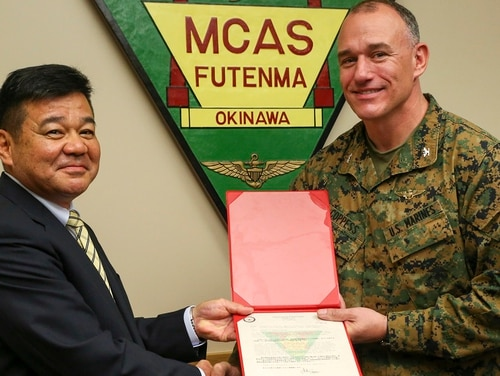 Police Chief Osamu Hamada, left, accepts a letter of appreciation from Col. Mark Coppess during an award ceremony March 8, 2018, on Marine Corps Air Station Futenma, Okinawa, Japan. (Pfc. Nicole Rogge/Marine Corps)