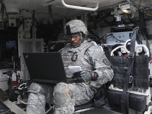 A Cyber Soldier assigned to the 780th Military Intelligence Brigade prepares his equipment inside a Stryker vehicle during an integrated cyber exercise at Joint Base Lewis-McChord, Washington Oct. 21, 2015. The training integrates infantry ground units with cyber, signal and human intelligence collection capabilities, which gives units on the modern battlefield a broader capacity to search out and isolate their enemies in real time. (Capt. Meredith Mathis)