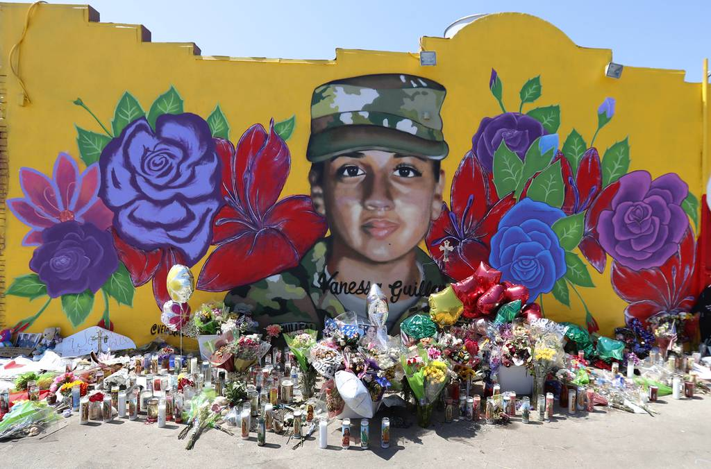Offerings sit in front of a mural of slain Army Spc. Vanessa Guillen painted on a wall in the south side of Fort Worth, Texas, July 11, 2020.
