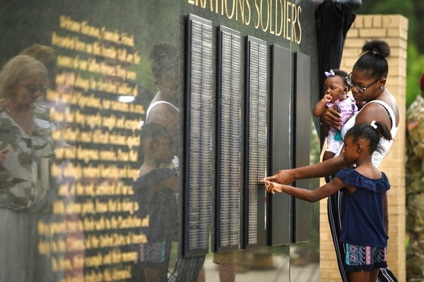 In this Thursday, May 24, 2018, photo, Sgt. La David Johnson's wife, Myeshia Johnson, and their two daughters, stand in front of the memorial wall touching his name plate during the U.S. Army Special Operations Command Fallen Special Operations Soldier Memorial ceremony on Fort Bragg, N.C. Johnson died on Oct. 4, 2017, from small arms fire while deployed in Niger. (Andrew Craft /The Fayetteville Observer via AP)