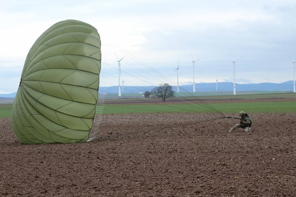A U.S. Army paratrooper lands at Alzey drop zone Dec. 18, 2019, after jumping off a C-160 during Operation Toy Drop 2019, at Alzey, Germany. (Staff Sgt. Sinthia Rosario/U.S. Army)