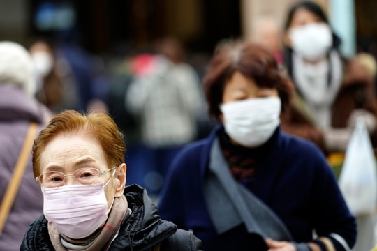 Pedestrians wear protective masks as they walk through a shopping district in Tokyo on Jan. 16. A man treated for pneumonia after returning from China tested positive for the new coronavirus identified as a possible cause of an outbreak in the Chinese city of Wuhan. (Eugene Hoshiko/AP)