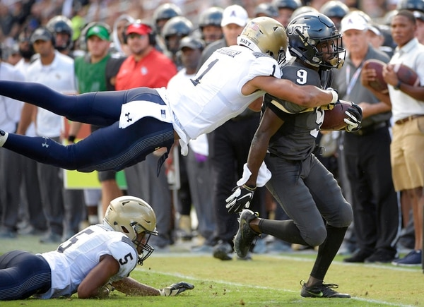 Central Florida running back Adrian Killins Jr. is tackled by Navy safety Jacob Springer after rushing as defensive back Michael McMorris watches. (Phelan M. Ebenhack/AP)
