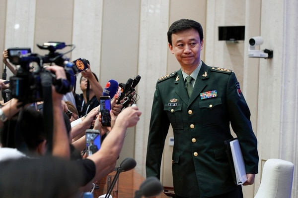 China's Defense Ministry spokesman Wu Qian disregards reporters asking questions after a press conference at the State Council Information Office in Beijing on Wednesday. (Andy Wong/AP)