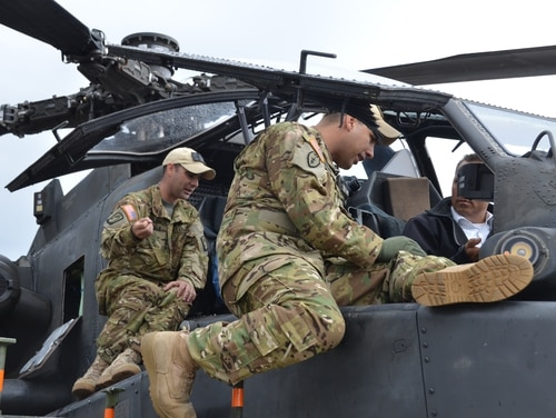 Army Chief Warrant Officer 2 Chad Remala, left, and Chief Warrant Officer 2 Victor Reyna, both pilots with the Army's 12th Combat Aviation Brigade, describe the instruments in the AH-64 Apache helicopter cockpit. The Air Force considered reviving its long-dormant warrant officer program in an effort to alleviate the pilot shortfall crisis, but has decided it wouldn't help. (Army)