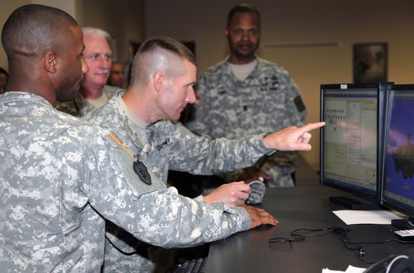 Staff Sgt. Deante J. Long, Stryker Maintenance Course instructor, demonstrates the interactive classroom training to Command Sgt. Maj. Daniel A. Dailey, U.S. Army Training and Doctrine Command command sergeant major, during a visit here May 23. Students in the Stryker Maintenance Course virtually troubleshoot problems with the vehicle before participating in the hands-on portion. Instructors monitor the students' progress from a main control station.