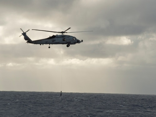 An MH-60R Sea Hawk assigned to the Raptors of Helicopter Maritime Strike Squadron 71 dips an airborne low-frequency sonar sensor in 2016. (Navy)