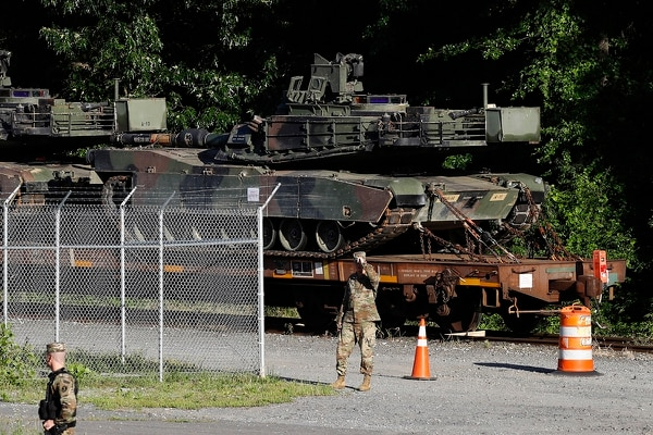 Military police walk near Abrams tanks on a flat car in a rail yard, Monday, July 1, 2019, in Washington, ahead of a Fourth of July celebration that President Donald Trump says will include military hardware. (Patrick Semansky/AP)
