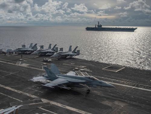 An F/A-18E Super Hornet lands on the flight deck of the USS Ronald Reagan (CVN 76), as USS Nimitz (CVN 68) steams alongside in the South China Sea, July 6, 2020. (MC2 Samantha Jetzer/U.S. Navy via AP)