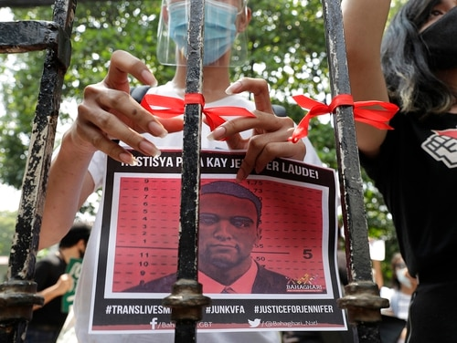 A demonstrator ties a red ribbon on a gate of the Department of Justice to symbolize their protest while holding a picture of U.S. Marine Lance Cpl. Joseph Scott Pemberton during a rally in Manila, Philippines, on Thursday, Sept. 3, 2020. (Aaron Favila/AP)