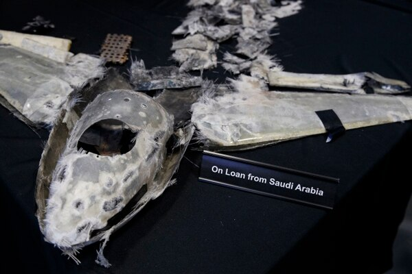 Debris that was an unmanned aerial vehicle is displayed with a sign that reads