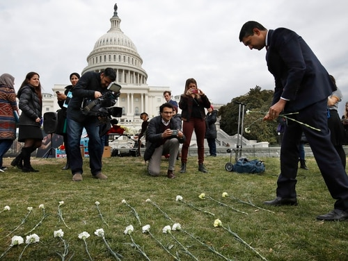 Rep. Ro Khanna, D-Calif., places flowers among 5,000 flowers near the Capitol that activists said are to memorialize 5,000 children killed by Saudi bombings in Yemen, on March 19, 2018. (Jacquelyn Martin/AP)