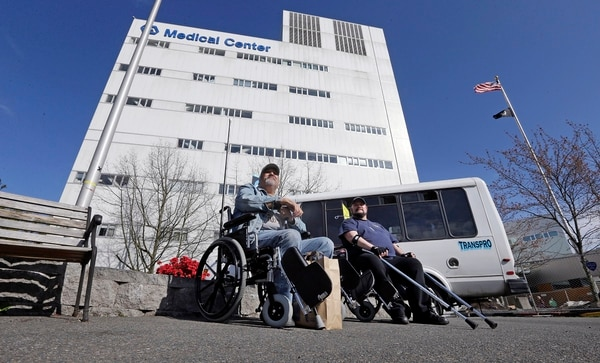 Army veteran Michael Thrun, left, and Navy veteran Thomas Berry sit in wheelchairs as they wait for their rides following treatment at the VA Puget Sound Medical Center in Seattle in March 2015. (Elaine Thompson/AP)