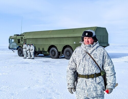 A Russian officer, right, and soldiers stand next to a special military truck at the Russian northern military base on Kotelny island, beyond the Arctic Circle on April 3, 2019. The Russian military base dubbed the