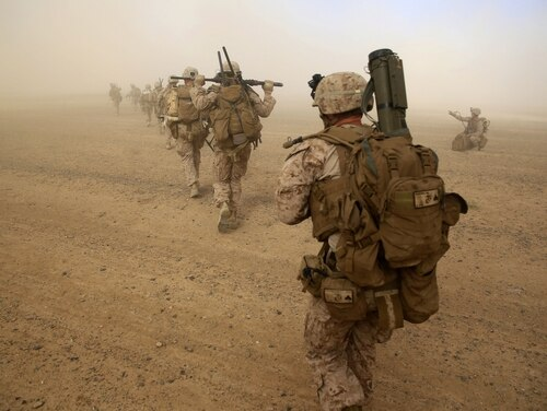 Marines with Weapons Company, 1st Battalion, 7th Marine Regiment, run to security positions after offloading from a CH-53E Super Sea Stallion helicopter during a mission in Helmand province, Afghanistan, April 28, 2014. The company's mission was to disrupt Taliban forces in Larr Village and establish a presence in the area. (Marine Corps)