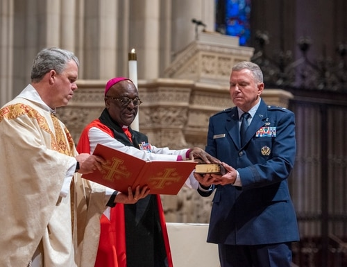 The Very Rev. Randolph Hollerith, dean of the Washington National Cathedral, left, and the Right Rev. Carl Wright, bishop suffragan for the armed ofrces and federal ministries in the Episcopal Church, center, bless the official Bible of the newly created Space Force during a service at the cathedral on Jan. 12. Maj. Gen. Steven Schaick, the Air Force's chief of chaplains, is holding the Bible on the right. The cathedral said in a social media post that the Bible will be used to swear in all Space Force commanders, drawing a strong objection from the Military Religious Freedom Foundation. (Danielle Thomas/Washington National Cathedral)