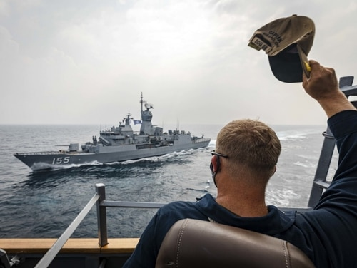 Cmdr. Ryan Easterday, commanding officer of the guided-missile destroyer John S. McCain, waves to the Australian frigate HMAS Ballarat Tuesday during the Malabar 2020 exercise. (MC2 Markus Castaneda/Navy)