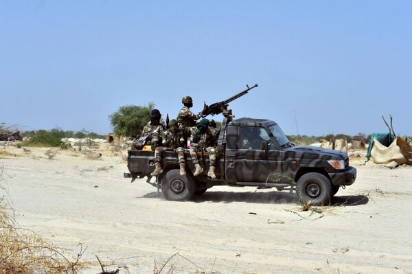 Niger soldiers ride in a military vehicle. (Photo credit should read ISSOUF SANOGO/AFP/Getty Images)
