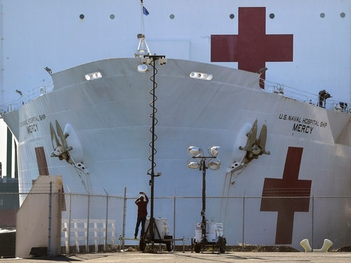 In this March 27, 2020, file photo, a pedestrian takes a picture of the USNS Mercy as it docks at the Port of Los Angeles. (Mark J. Terrill/AP)
