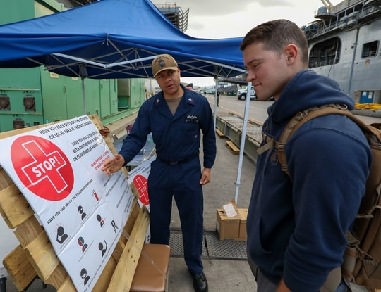 SAN DIEGO (March 25, 2020) – Hospital Corpsmen 1st Class Jonathan Ivey, left, screens Ensign Mackenzie Jones for signs of the coronavirus before allowing him to board the amphibious assault ship USS Makin Island (LHD 8). Makin Island has a 24-hour medical screening station at the brow of the ship; all hands must pass through this station when coming aboard the ship. (US Navy photo by Mass Communication Specialist 2nd Class Jeremy Laramore)