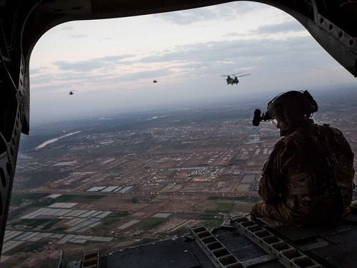 U.S. Army AH-64D Apache Longbow helicopters escort two CH-47 Chinook helicopters over Taji, Iraq. (Cpl. Andre Dakis/Marine Corps)