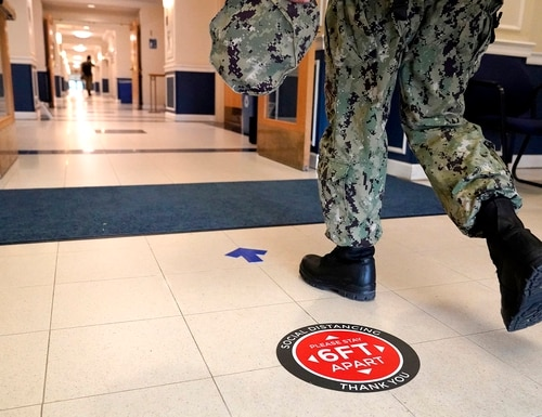 A social distancing sign is seen on the floor as a midshipman walks to class at Luce Hall at the U.S. Naval Academy, Aug. 24, 2020, in Annapolis, Md. (Julio Cortez/AP)
