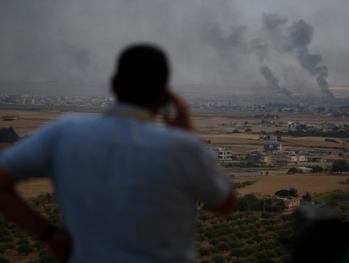 A journalist in southeastern Turkey watches as smoke billows from targets in Ras al-Ayn, Syria, during bombardment by Turkish forces on Oct. 16, 2019. (Lefteris Pitarakis/AP)
