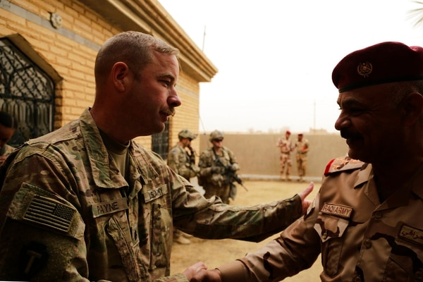 In this Jan. 25, 2018, photo, U.S. Army Lt. Col. Brandon Payne meets with his Iraqi counterpart at a small complex in the town of Qaim. (Susannah George/AP)