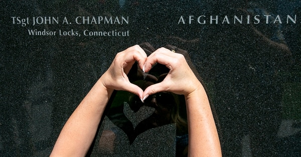 A family friend makes a heart next to the engraving for Tech. Sgt. John Chapman on the Wall of Honor at the Air Force Memorial Aug. 24. (Alan Lessig/Staff)