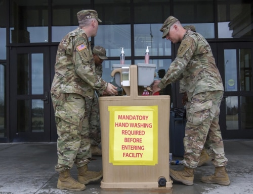 A group of 1st Infantry Division Soldiers wash their hands at the designated hand washing stations just outside the 1st Infantry Division Headquarters, Fort Riley, March 18, 2020. Mandatory hand washing is required before entering the facility. (U.S. Army Photo by Spc. Brandon Bruer)