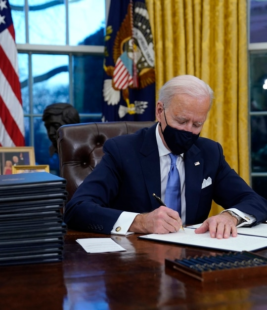 President Joe Biden signs his first executive order in the Oval Office of the White House on Wednesday, Jan. 20, 2021, in Washington.(Evan Vucci/AP)