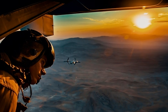 """Sgt. Derek Levi, MV22 crew chief, Marine Medium Tilt Rotor Squadron, Marine Aircraft Group 16, 3rd Marine Aircraft Wing looks over the landscape of Marine Corps Air Ground Combat Center, Twentynine Palms, Calif., during an aerial flight formation exercise August 12, 2018. """"I get to see the world from the sky,"""" said Sgt. Derek Levi, MV22 crew chief, Marine Medium Tilt Rotor Squadron, Marine Aircraft Group 16, 3rd Marine Aircraft Wing. (Lance Cpl. Rachel K. Young/Marine Corps)"""