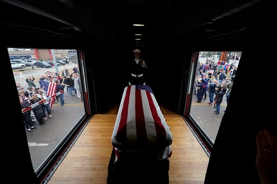 The flag-draped casket of former President George H.W. Bush passes through Magnolia, Texas, Thursday, Dec. 6, 2018, along the train route from Spring to College Station, Texas. (David J. Phillip/AP Pool)