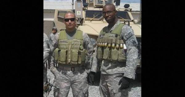Derrick Miller on deployment in front of up-armored vehicles and wearing a belt of 40mm ammunition. (United American Patriots)