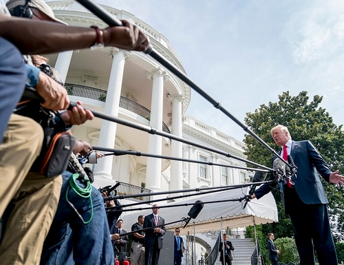 President Donald Trump speaks to members of the media before boarding Marine One on the South Lawn at the White House in Washington, Friday, Aug. 17, 2018, for a short trip to Andrews Air Force Base, Md., and then on to Southampton, N.Y., for a fundraiser. (Andrew Harnik/AP)