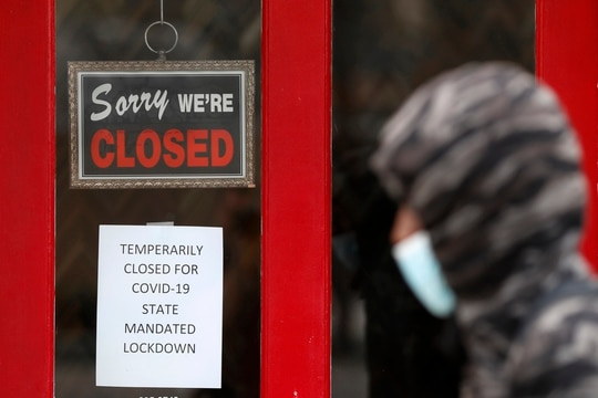 A pedestrian walks by The Framing Gallery, a business closed due to the COVID-19 pandemic, in Grosse Pointe, Mich., on May 7, 2020. (Paul Sancya/AP)
