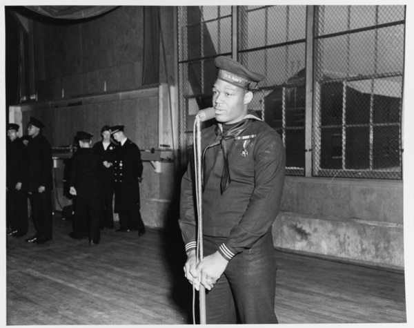 Mess Attendant 1st Class Doris Miller speaking during a visit to the Naval Training Station, Great Lakes, Illinois, on 7 January 1943. He is wearing the Navy Cross medal, awarded for heroism during the Pearl Harbor Attack, 7 December 1941. (National Archives)