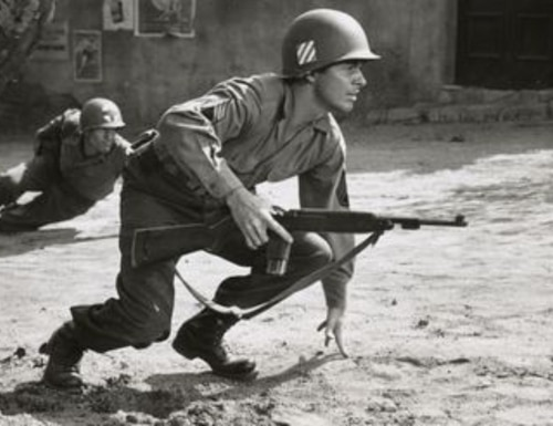 """Movie still from Universal Studio's production of """"To Hell and Back"""", 1955, starring Audie Murphy. In the film's final scene, as Murphy receives the Medal of Honor, images of his fallen comrades drift onto the screen. Murphy wanted Americans to know that his fellow infantrymen were deserving as he of the award. (National Museum of American History, Smithsonian Institution)"""