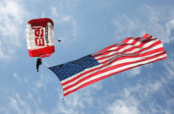 MIAMI BEACH, FL - NOVEMBER 11: Mike Elliott, from the All Veteran Parachute Team, soars through the air with an American flag during a Veterans day ceremony on November 11, 2015 in Miami Beach, Florida. Originally established as Armistice Day in 1919, the holiday was renamed Veterans Day in 1954 by President Dwight Eisenhower, and honors those who have served in the U.S. military. (Photo by Joe Raedle/Getty Images)