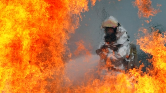 A firefighter extinguishes a fire started from a simulated plane crash at Osan Air Base, South Korea, during an exercise on July 23, 2012. (Staff Sgt. Craick Cisek/Air Force)