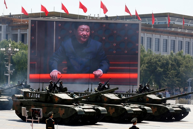 Chinese President Xi Jinping is displayed on a screen as Type 99A2 Chinese battle tanks take part in a parade commemorating the 70th anniversary of Japan's surrender during World War II held in front of Tiananmen Gate in Beijing, Sept. 3, 2015. (Ng Han Guan/AP)