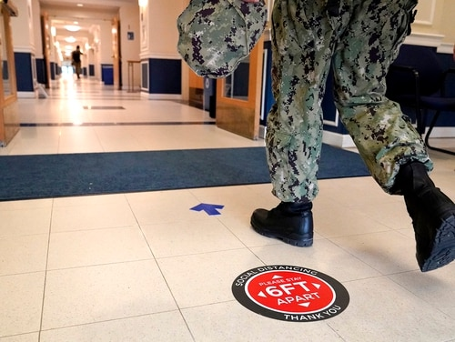 A social distancing sign is seen on the floor as a midshipman walks to class at Luce Hall at the U.S. Naval Academy, Monday, Aug. 24, 2020, in Annapolis, Md. (Julio Cortez/AP)