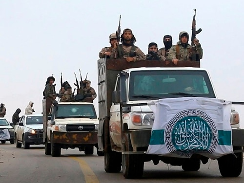 This photo released Dec. 4, 2018, by the al-Qaida-affiliated Ibaa News Agency, shows al-Qaida-linked fighters driving their vehicles during a military drill in northern Syria. (Ibaa News Agency via AP)