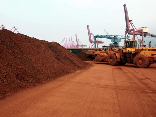 In a picture taken on September 5, 2010 a man driving a front loader shifts soil containing rare earth minerals to be loaded at a port in Lianyungang, east China's Jiangsu province, for export (STR/AFP/Getty Images)